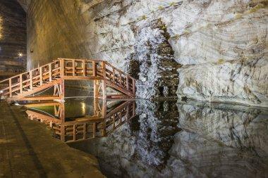 Wooden bridge reflection in underground salt mine lake