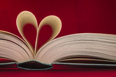 Blurry heart made from book pages over red background. Valentines theme.