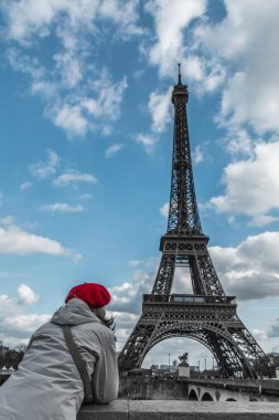 Young tourist woman with Parisian style red hat looking at Eiffel tower from the Seine river side