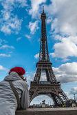 Frau junge Touristen mit Blick auf den Eiffelturm von der Flussseite Seine Pariser Stil rot-Hut