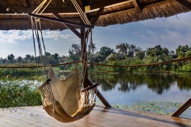 Chair hammock in the arbor on nature background. Peaceful view on the lake from wooden gazebo.