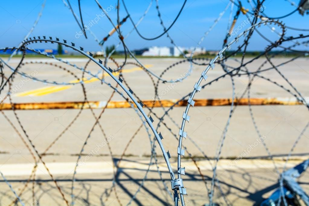 Close-up of a barbed wire fence. Horizontal view of a barbed wir ...
