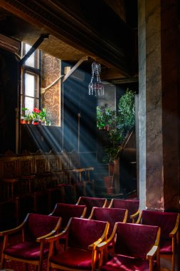 Sun rays over church window inside. A dim old church interior li