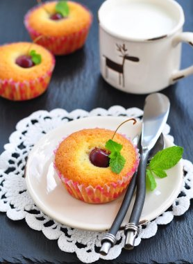 Cakes with sweet cherry and cup milk on a black background