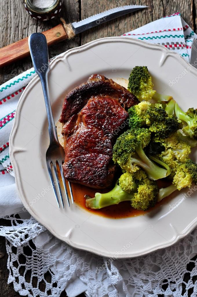 Grilled ribeye steak with boiled broccoli in olive oil and sea salt