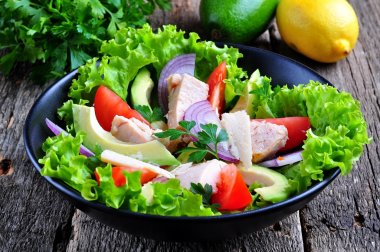 Healthy salad of avocado, tomatoes, canned tuna, onions and lettuce with parmesan, parsley and olive oil