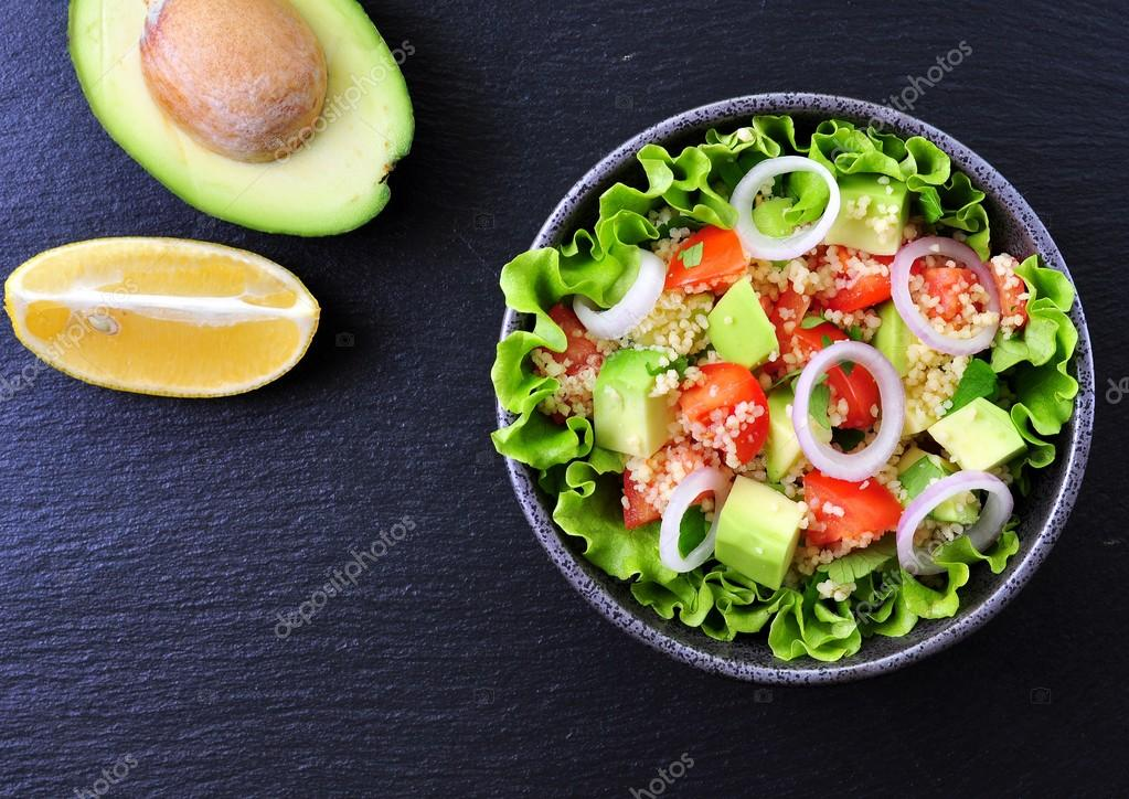 Vegetarian couscous salad, avocado, tomatoes, red onion with olive ...