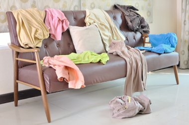 Messy clothes scattered on a sofa in living room