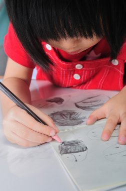 3 years old asian girl draws and sketchs many human faces with p