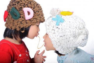 two asian children eating fish snack together