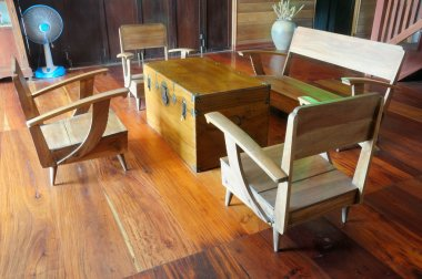 a teak wood console table and armchair on wooden floor