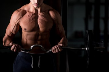 Muscular man lifting a barbell in gym