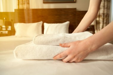 Maid changing towels in hotel room