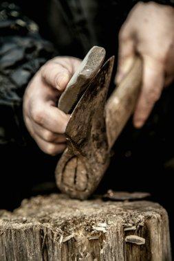 Male hands grinding a hatchet on log