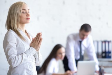 Corporate woman meditating at work