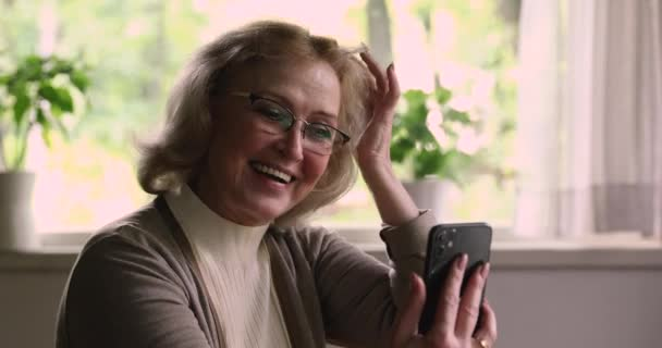 55-jährige Frau hält Smartphone-Gespräche per Videokonferenz per Konferenz-App