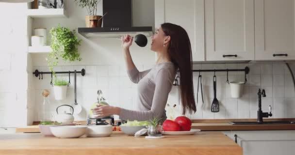 Glücklich entspannte junge Frau singt Lied in der Kelle in der Küche.