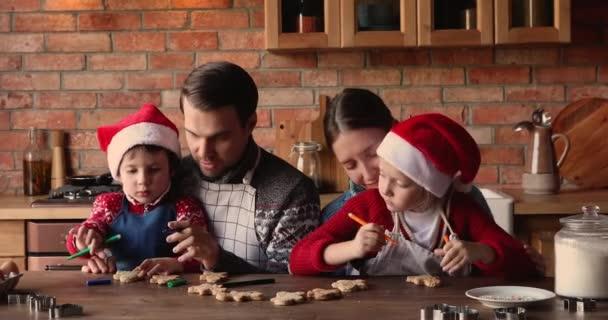 Glückliche Familie mit kleinen Kindern schmücken selbstgebackene Weihnachtsplätzchen