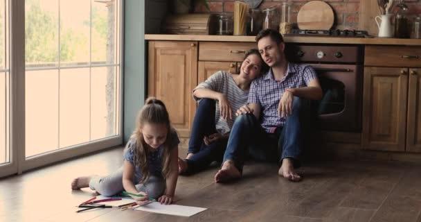 Rodina tráví čas doma sedět na podlaze v kuchyni