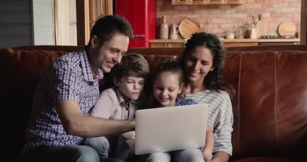 Pár s dětmi tráví čas na internetu pomocí notebooku