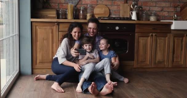 Family sitting on floor in kitchen having fun using smartphone