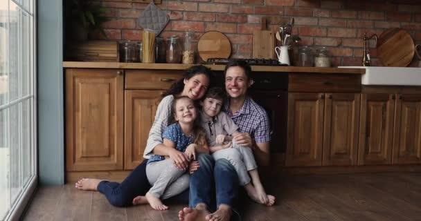 Celá rodina sedí v kuchyni na podlaze a usmívá se na kameru