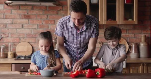 Otec a malé děti společně připraví salát v domácí kuchyni