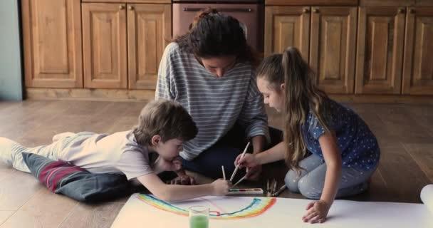 Mutter und Kinder sitzen auf dem Boden und malen mit Farben