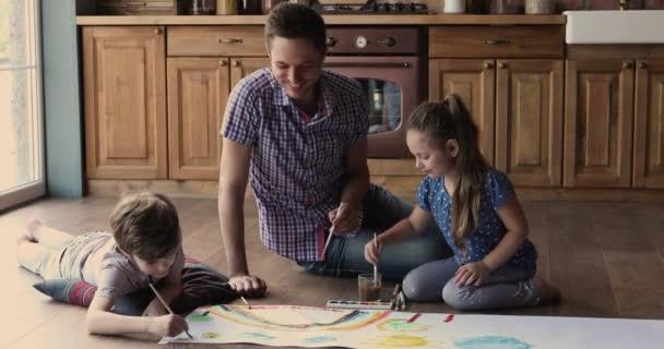 Papa und kleine Kinder malen mit Farben auf Papierbogen
