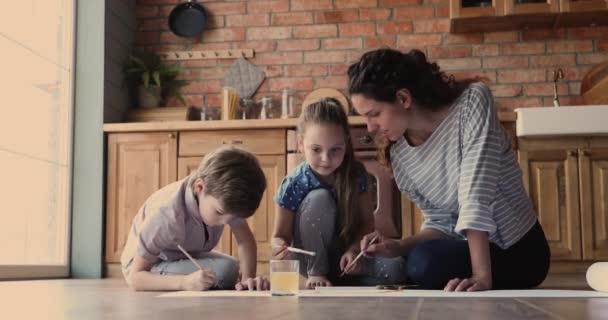 Mutter und Kinder sitzen drinnen und malen mit Farben auf Papier