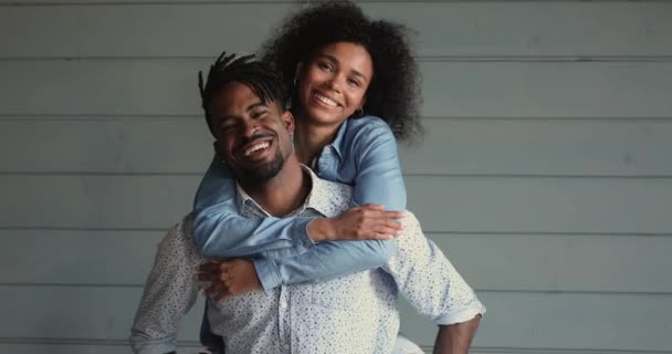Happy african wife piggybacking husband posing on wooden wall background