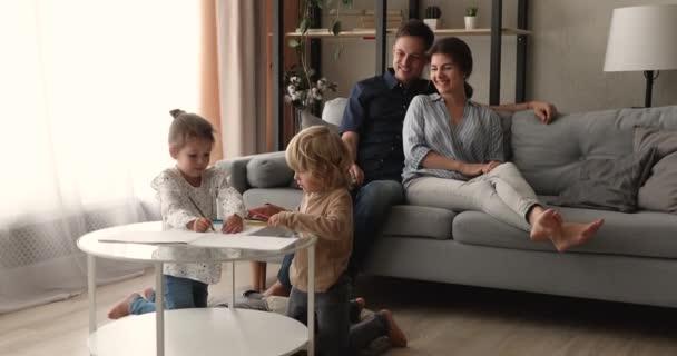 Šťastní rodiče relaxaci na gauči děti kreslení v skicáku
