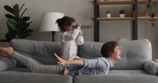 Glückliche Mutter spielt mit kleiner Tochter zu Hause