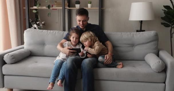 Papa und Kinder sitzen auf Couch und haben Spaß mit Smartphone