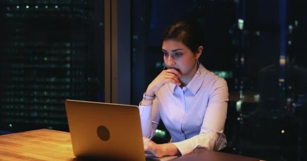 Indische Geschäftsfrau arbeitet nachts Überstunden am Laptop im Büro