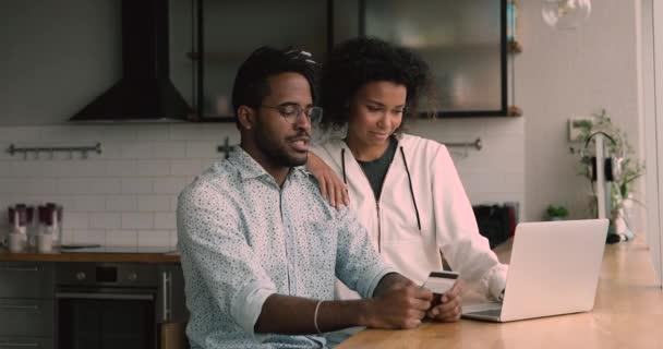 Afrikanisches Paar kauft im Internet mit Kreditkarte und Laptop