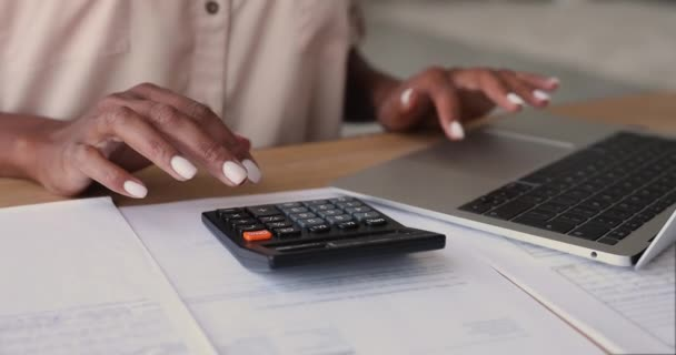 African woman calculates costs using calculator and laptop app, closeup