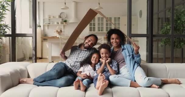 Afrikanische Familie mit Kindern sitzt auf Couch unter Kartondach
