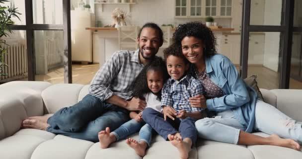 Schöne afrikanische Familie mit kleinen Kindern auf der Couch