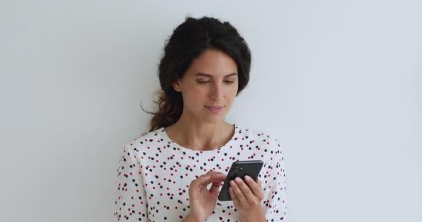 Glückliche Millennial-Frau beim Ansehen von Foto oder Video auf dem Smartphone.