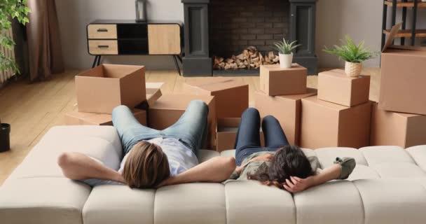 Entspanntes junges Familienpaar liegt am Umzugstag auf Sofa.