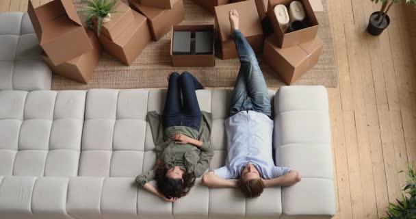 Millennial-Ehepaar entspannt sich am Renovierungstag auf der Couch.
