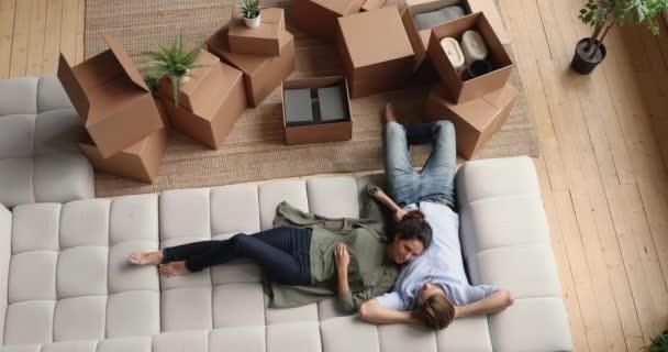 Liebevolles junges Familienpaar entspannt auf Sofa, diskutiert über Umzug.