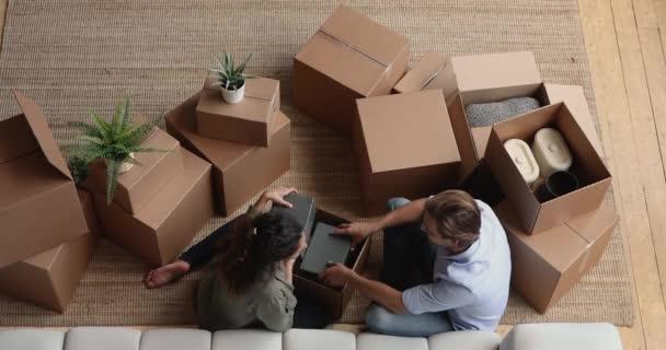 Glückliches junges Familienpaar packt persönliche Sachen im neuen Zuhause aus.
