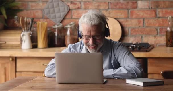 Älterer Mann trägt Kopfhörer und nutzt Laptop-Gespräch per Videokonferenz