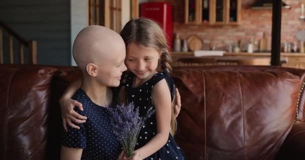 Malá dcera a matka rakovina pacient sedět uvnitř drží květiny