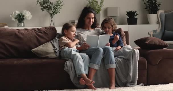 Loving mother reading book to little children