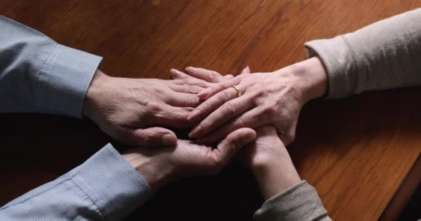 Mitfühlende Frau mittleren Alters streichelt faltige Hände eines älteren Mannes.