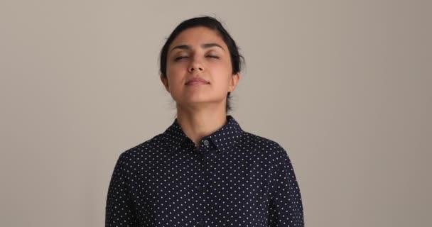 Ruhige, achtsame junge indische ethnische Frau atmet frische Luft.