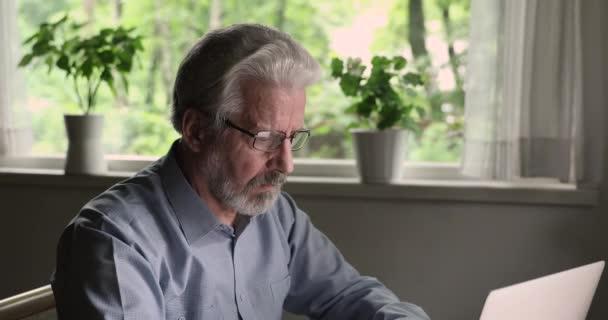 Alter Mann nimmt Brille ab und macht Pause bei der Computerarbeit